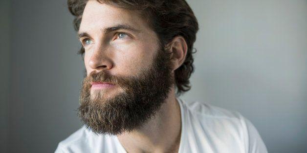 Pensive bearded brunette man looking away