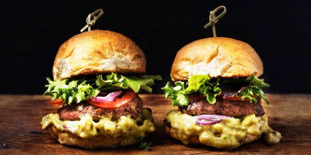 Two burgers on a rustic wooden table