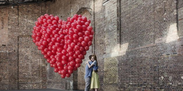 Couple hugging in empty warehouse with red heart made of balloons