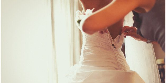 A shot of a bride getting into her wedding dress taken from a lower angle as the back of the dress is being done up from the help of her mother.