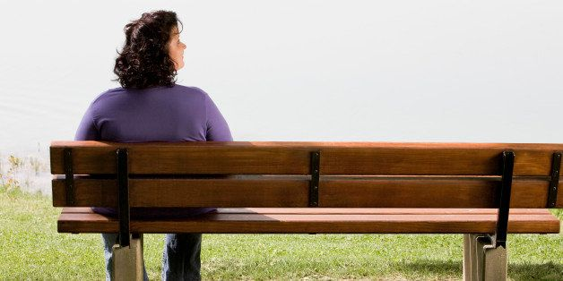 rear view of overweight woman sitting on park bench near lake