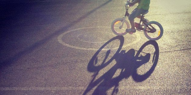 Long shadow of child riding a bicycle