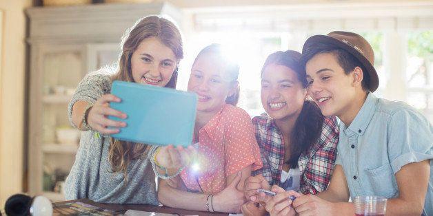 Group of smiling teenagers taking selfie in dining room