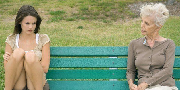 Teenage girl sitting apart from grandmother on bench, arms folded, looking down