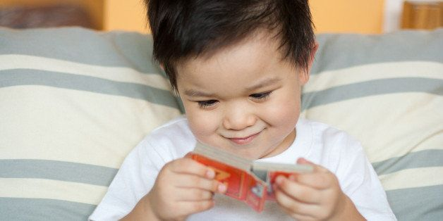 Cute toddler boy with amusing smirk on face reading small board book.