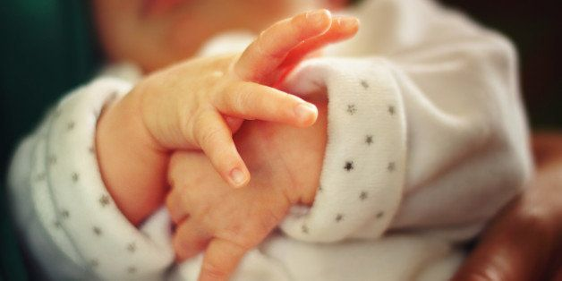 Closeup of small hands of a newborn baby separating the little fingers.Baby is held in the mother's arms.
