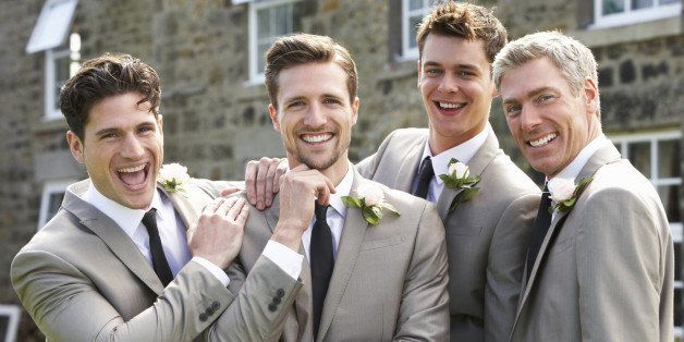 groom with best man and groomsmen at wedding smiling to camera