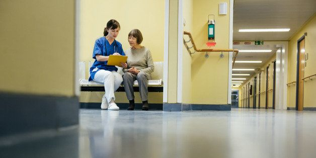 Mature female doctor and senior patient doing paperwork at hospital reception area