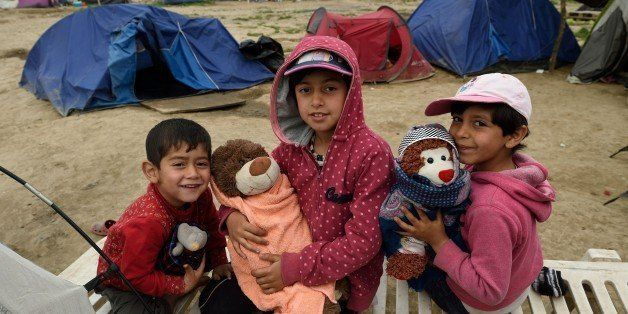 Refugee children pose for a photograph with their toys at the makeshift camp at the Greek-Macedonian border near the village of Idomeni, on April 14, 2016.