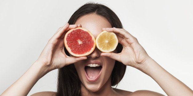 Funny portrait of young brunette woman holding fresh lemon and grapefruit. Healthy eating lifestyle and weight loss concept. Studio white background.
