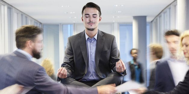 Germany, Neuss, Business man meditating on desk