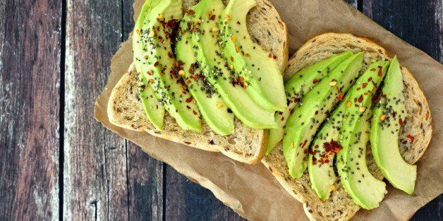 Open avocado sandwiches with whole grain bread on paper against a rustic wooden background