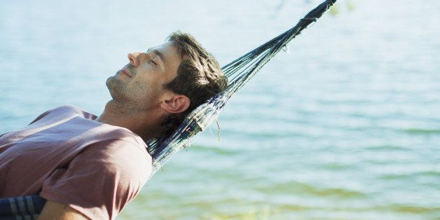 Serene man laying in hammock at lakeside