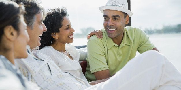 Smiling mature couples sitting on patio at resort