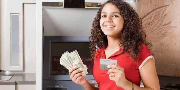 African teenage girl holding money and credit card