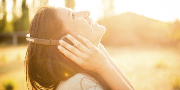 Young happy caucasian woman listening music in the nature with her modern ear phone, during the sunset.