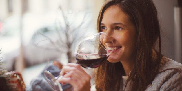 Beautiful happy lady drinking glass of red wine.