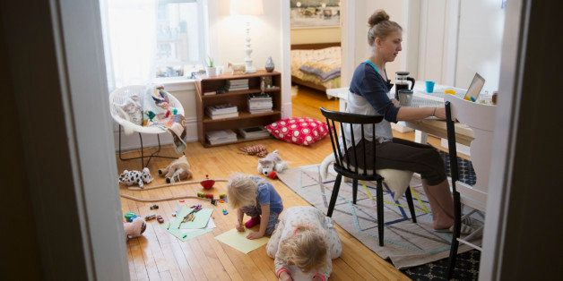 Mother working from home while children play