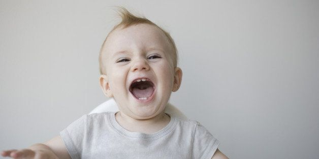 Laughing baby in highchair
