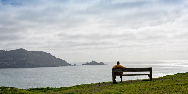 Woman sitting on a wooden bench  overlooking Pacific Ocean