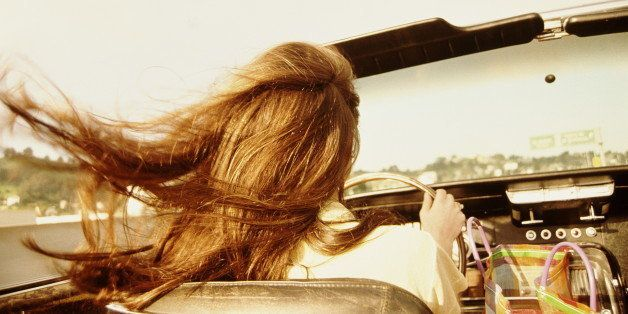 Woman driving convertible car, rear view