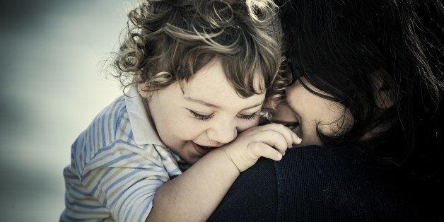 Mom holding smiling son