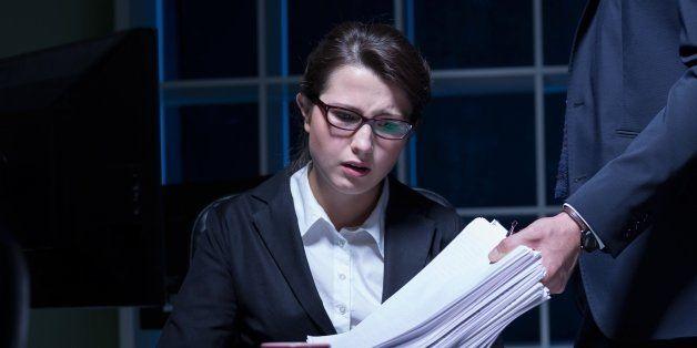 Sleepy woman working overtime in office