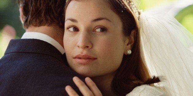 Doubtful bride embracing groom
