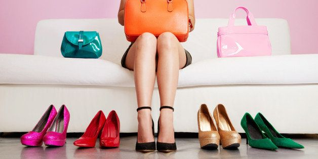 Woman with beautiful legs holding bag. Many colours heels and bags. Shopping,choosing fashion items.
