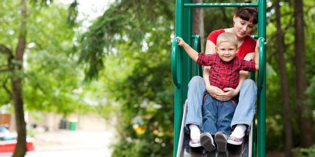 Mother and son on top of slide at playground