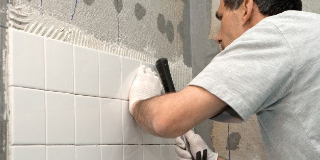 man setting tile on cement...