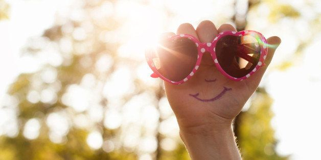 Hand with a smiling face drawn on palm, holding a pair of heart shaped sunglasses up to the sun.