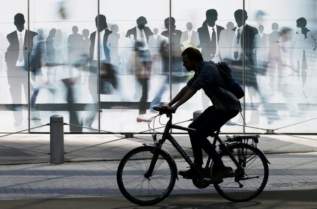 A man rides a bicycle past a building of the European Commission in