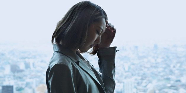 Depressed young woman,cityscape in background