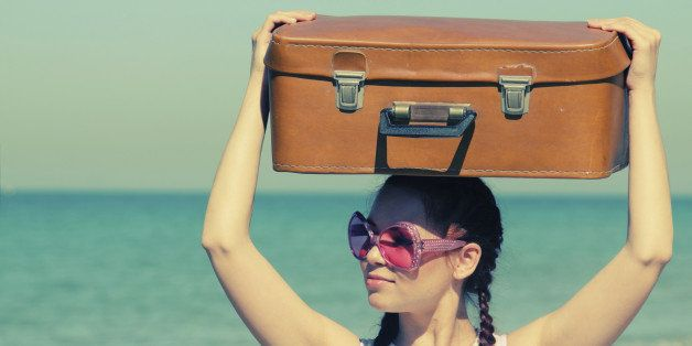 woman with suitcase on the beach. Photo in old image style.