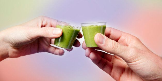 Close up of young woman and man's hands toasting with green smoothie shots