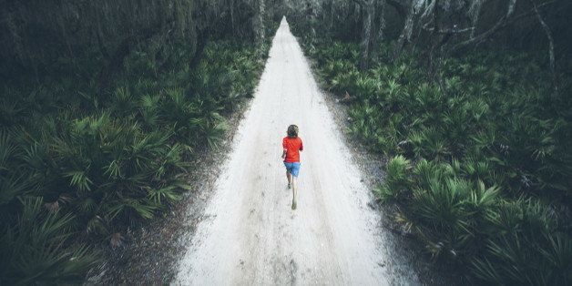 A solitary male runner out for a training run on rural road at sunset on Cumberland Island off the coast of Georgia.