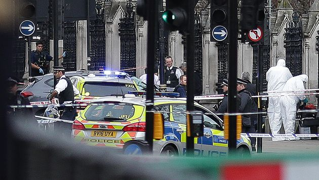 Armed police officers stand guard, as forensics officers work around the vehicle Khalid Masood crashed...