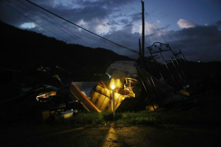 A donated solar lamp in a driveway illuminates storm debris still waiting to be collected on Dec. 25, 2017, in Morovis,