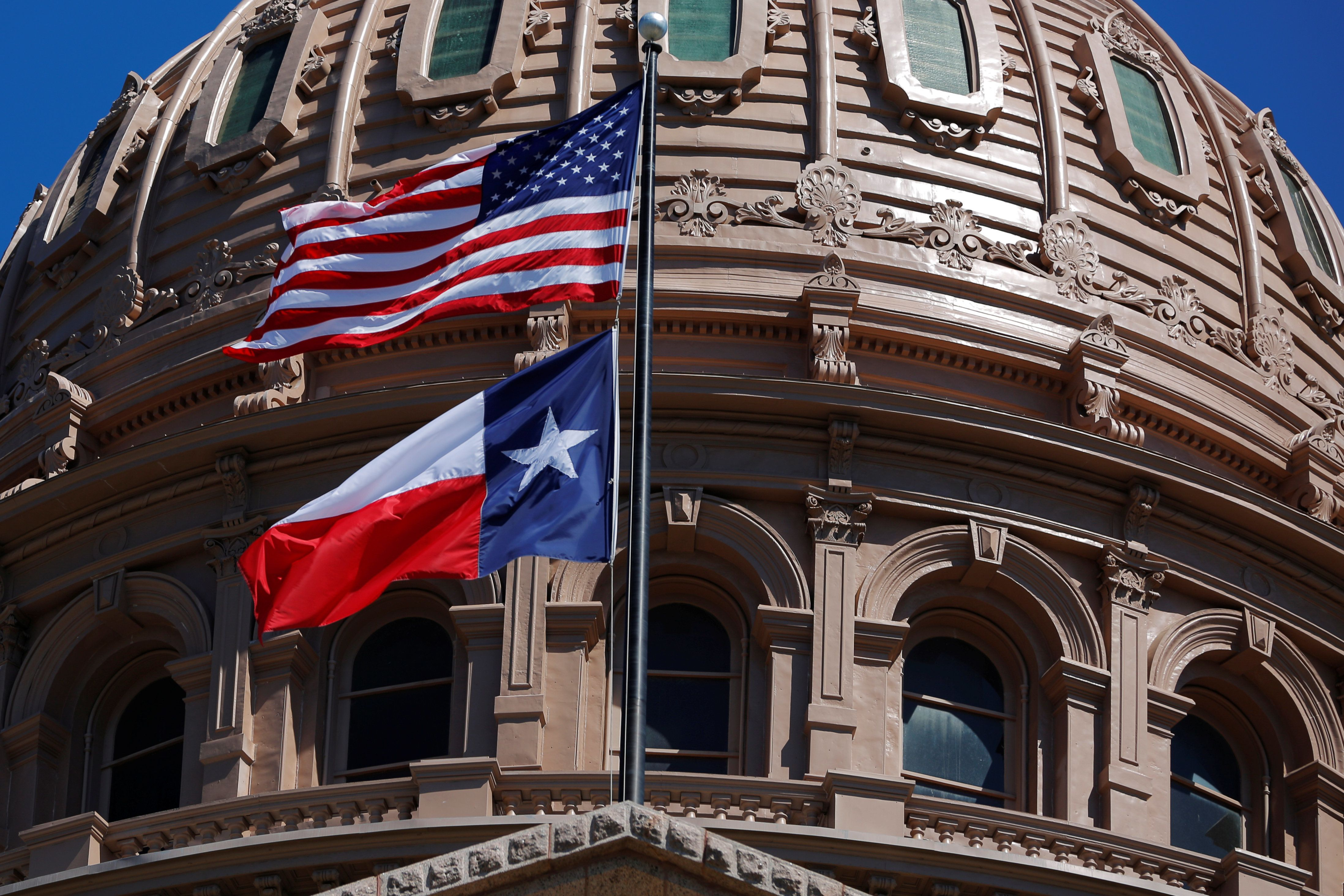 The U.S flag and the Texas State flag fly over the Texas State Capitol as the state senate debates the #SB6 bathroom bill in Austin, Texas, U.S., March 14, 2017. REUTERS/Brian Snyder