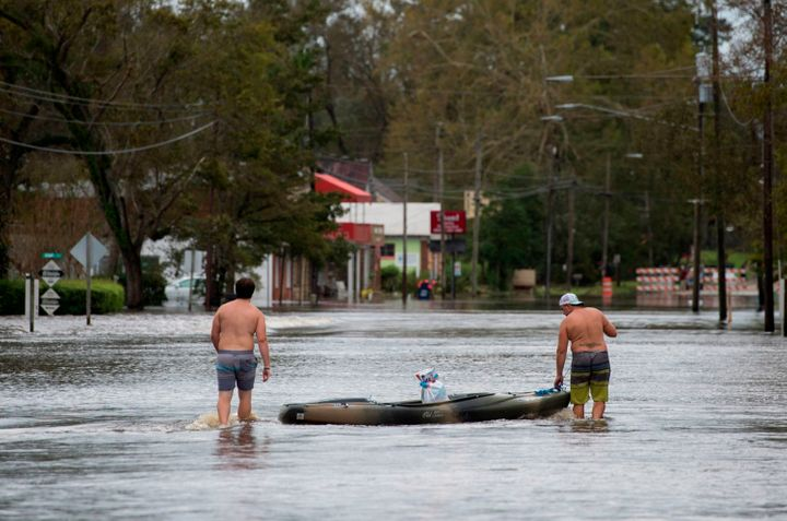 Two men use a kayak to carry supplies across a road flooded by Hurricane Florence in Pollocksville, North Carolina, on Septem