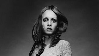 Twiggy wearing a knit baby-doll dress with ribbed bodice by Juliano Knits, with thigh- high socks, a choker by Mary Smith, and braids by Edith Imre; she tugs at the hem of her dress. (Photo byJustin de Villeneuve/Condé Nast via Getty Images)