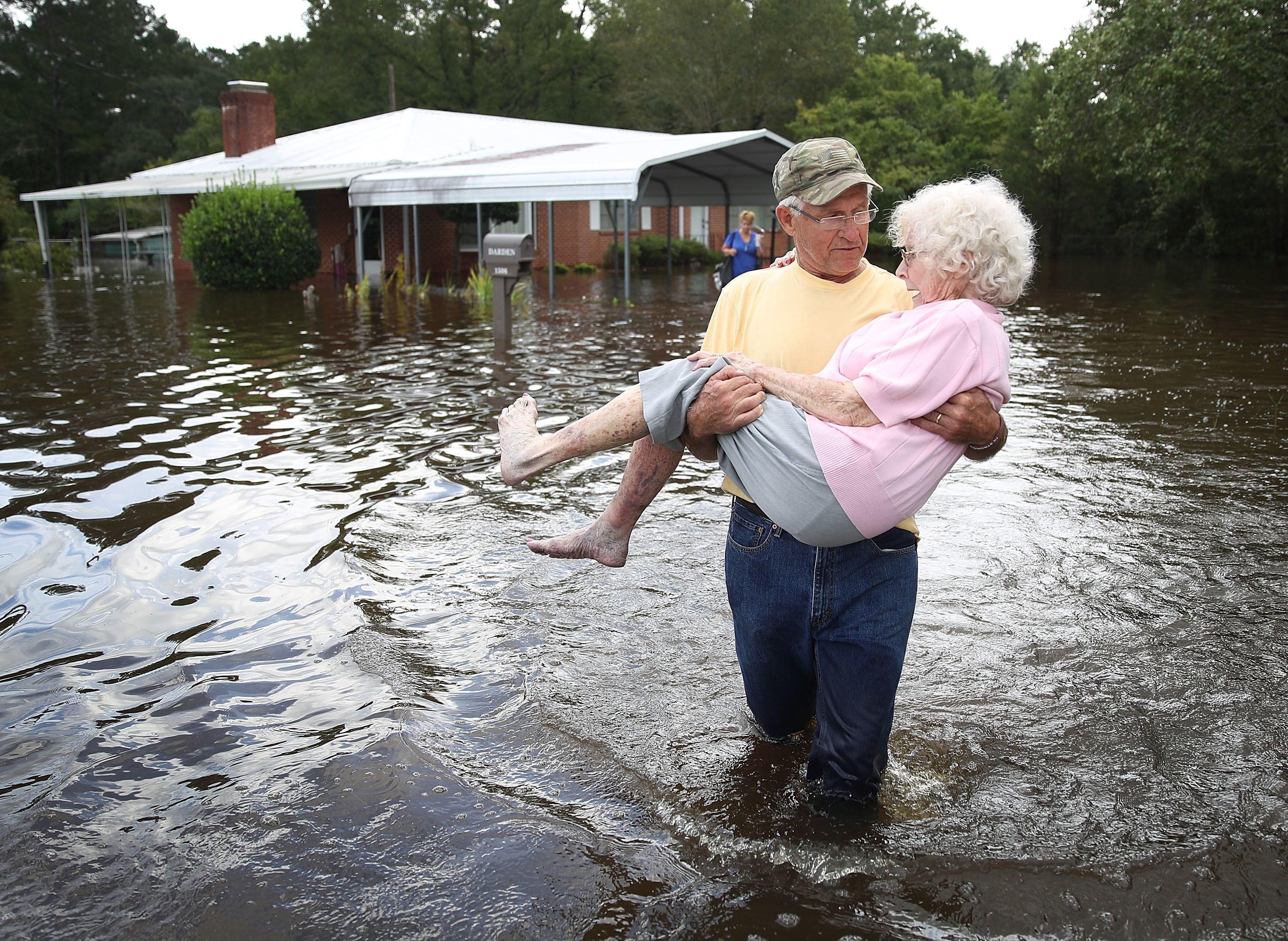 Bob Richling carries Iris Darden as water from the Little River starts to seep into her home on Monday...