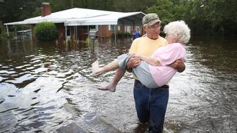 SPRING LAKE, NC - SEPTEMBER 17:  Bob Richling carries Iris Darden as water from the Little River starts to seep into her home on September 17, 2018 in Spring Lake, North Carolina. Flood waters from the cresting rivers inundated the area after the passing of Hurricane Florence.  (Photo by Joe Raedle/Getty Images)