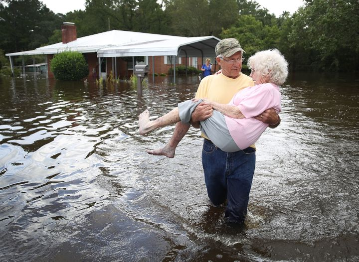 Bob Richling carries Iris Darden as water from the Little River starts to seep into her home on Monday in Spring Lake, North