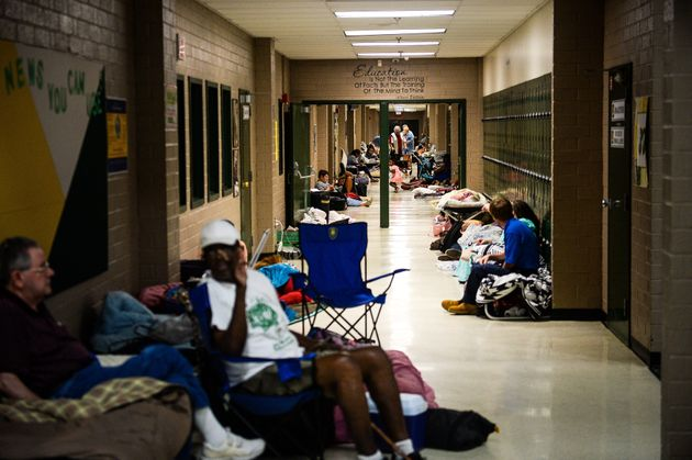 Residents sit in the hallway of a temporary Red Cross shelter at Conway High School ahead of Hurricane...