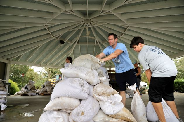 A Boy Scout volunteer and his father help stack sandbags donated by the city of
