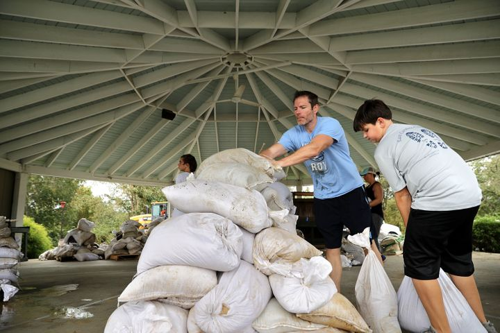 A Boy Scout volunteer and his father help stack sandbags donated by the city of Greenville.