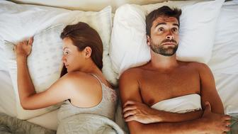 High angle shot of an arguing couple ignoring each other in bed