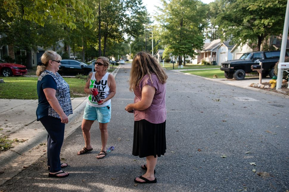 Pat Williams (left), Sally Leeman and Shannon Hicks gather in front of their homes to talk about the rising Cape Fear River,